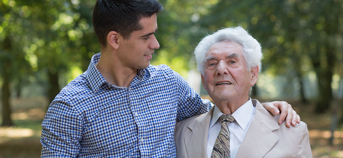 caring adult grandson with arm round his grandfather, both are smiling