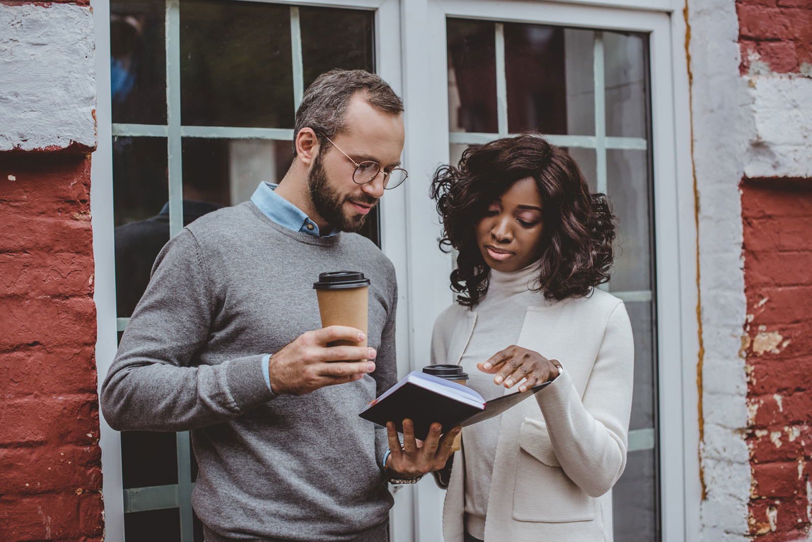 Male and female couple looking at a notebook together, man holding a cup of coffee